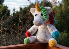 Colorful unicorn amigurumi in the forest royalty free stock photo