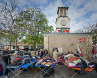 Colorful used clothing for sale at a flea market in Paris. PARIS, FRANCE OCTOBER 23, 2014  A man checks out a pair of pants at the popular flea market at the Royalty Free Stock Photography