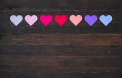 Seven Hearts in Various colors on rustic wood board background. Colorful Valentine`s Day Hearts in Pinks, Red, Purple, Lavender Tones laying on a Dark Rustic Royalty Free Stock Image