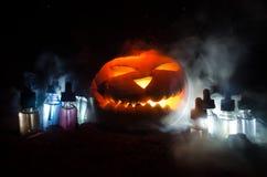 Colorful vape liquids with Halloween pumkin on dark background. Vape concept Stock Photos