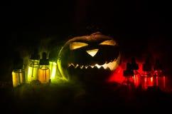 Colorful vape liquids with Halloween pumkin on dark background. Vape concept Stock Images