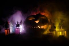 Colorful vape liquids with Halloween pumkin on dark background. Vape concept. Colorful vape liquids with Halloween pumkin on dark background. Vape Halloween royalty free stock photos