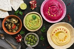 Colorful varied hummus, caponata, olives, pita and pomegranate on a dark rustic background. Vegetarian diet food.Top view, flat. Lay. Mediterranean food royalty free stock photo