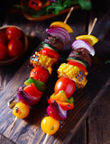 Colorful vegan vegetable skewers. With fresh roasted or grilled sweet peppers, onion, mushroom, corn, eggplant and cherry tomatoes, view from above on a wooden Royalty Free Stock Image
