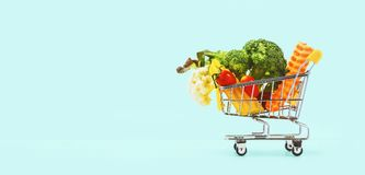 Colorful vegetables in the cart on blue. Background Stock Photos