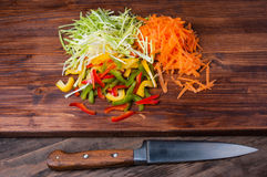 Colorful vegetables on a chopping board with knife. Shot a wooden desk Royalty Free Stock Photography