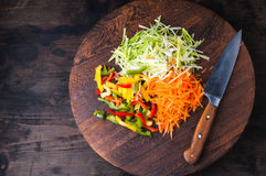 Colorful vegetables on a chopping board with knife. Shot a wooden desk Stock Images