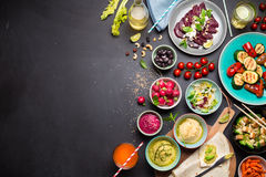 Colorful vegetarian feast dinner table from above. (top view). Healthy diet or lifestyle concept. Flat lay composition with free text space. Black chalkboard as royalty free stock image