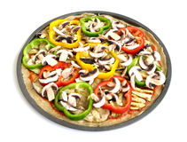 A colorful vegetarian pizza (top view). Top view of an uncooked vegetarian pizza with eggplant and zucchini slices with colorful capsicums and mushrooms Royalty Free Stock Images