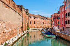 Colorful venetian cityscape. Boats on narrow canal between colorful houses and medieval brick wall under blue sky in Venice, Italy Royalty Free Stock Images