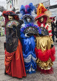 Colorful Venetian Costumes. Venice, Italy- February 18th, 2012: Image of a group of three persons wearing colorful costumes and masks in San Marco Square in Stock Photo