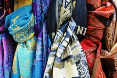 Colorful Venetian scarves background and texture. Colorful Venetian textile scarves background in blue, red, grey and beige hues Royalty Free Stock Images