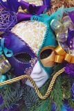 Colorful Venician Golden and Purple Carnival and Party Mask with feathers and ribbons in Winter Arrangement with Fir Branches. Ver royalty free stock photos