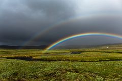 Rainbow Iceland. A colorful vibrant double rainbow arcs across lush grass under dark ominous clouds in the sky stock photo