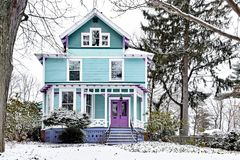 Brightly painted Victorian House Covered in Snow royalty free stock images