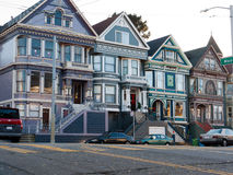 Colorful Victorian houses in San Francisco. Four similar victorian houses beautifully painted and decorated. Wide stairs lead to the entrances Royalty Free Stock Images