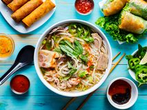Colorful vietnamese pho bo with beef and spring rolls. Shot from bird`s eye view royalty free stock images