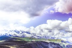 Colorful view of the mountain snow peaks. Under the clouds royalty free stock photos