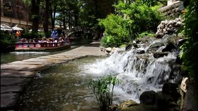 San Antonio River walk 7694. Colorful view of a tree lined section of the landmark San Antonio River Walk in San Antonio, Texas. People enjoying a lazy summer stock video footage