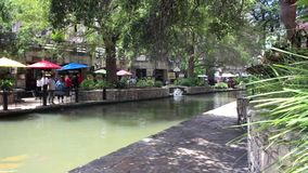 San Antonio River walk 7685. Colorful view of a tree lined section of the landmark San Antonio River Walk in San Antonio, Texas. People enjoying a lazy summer stock video