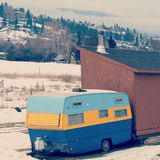 Colorful vintage camper. Light blue, yellow and dark blue. Parked next to brown building in winter field stock images