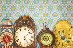 Colorful vintage clocks in front of retro wallpaper Royalty Free Stock Images