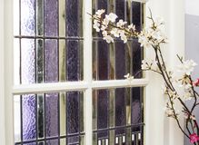 Colorful vintage window with stained glass and white flowers. In a old house royalty free stock image