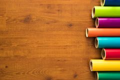 Colorful vinyl rolls on wooden background. With your necessary instruments Royalty Free Stock Photo