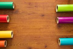 Colorful vinyl rolls on wooden background. With your necessary instruments Stock Photos