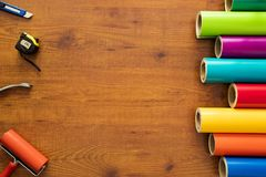 Colorful vinyl rolls on wooden background. With your necessary instruments Stock Photo