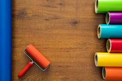 Colorful vinyl rolls on wooden background. With your necessary instruments Stock Images