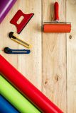 Colorful vinyl rolls on wooden background. A Colorful vinyl rolls on wooden background with your necessary instruments stock images