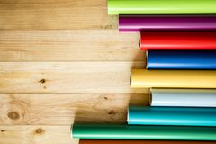 Colorful vinyl rolls on wooden background. A Colorful vinyl rolls on wooden background with your necessary instruments royalty free stock photography