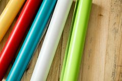 Colorful vinyl rolls on wooden background. A Colorful vinyl rolls on wooden background with your necessary instruments royalty free stock photos