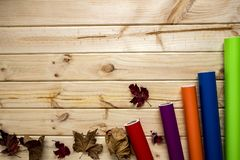 Autumnal colorful vinyl rolls on wooden background. Colorful vinyl rolls on wooden background placed in a row with autumn leaves royalty free stock images