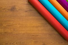 Colorful vinyl rolls on wooden background. With your necessary instruments Stock Photography