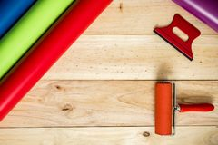 Colorful vinyl rolls on wooden background. A Colorful vinyl rolls on wooden background with your necessary instruments stock image