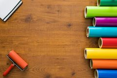 Colorful vinyl rolls on wooden background. With your necessary instruments and notebook Stock Photo