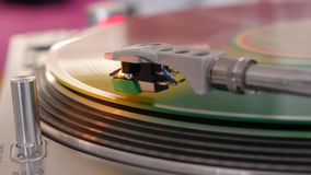 Colorful vinyl spinning on a record player close-up. Player turntable with it`s stylus running along a colorful vinyl record close-up stock video footage