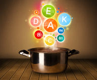 Colorful vitamins coming out from cooking pot Royalty Free Stock Images