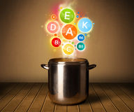 Colorful vitamins coming out from cooking pot Royalty Free Stock Photo