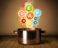 Colorful vitamins coming out from cooking pot Royalty Free Stock Photos