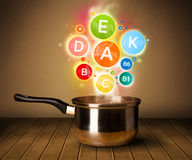Colorful vitamins coming out from cooking pot. Healthy food concept Stock Images