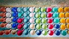 Colorful Vivid Ceramic Coffee Mugs On Sale on the Tiled Floor stock images