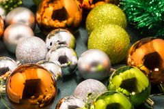 Colorful and vivid Christmas arrangement. Close Up view of Christmas golden balls with spangles and decorative wreath. Royalty Free Stock Photo