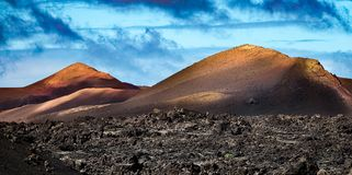 Colorful volcanic landscape background. Mountain range with lava fields in the foreground. Lanzarote, Canary Islands royalty free stock image