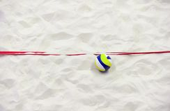 Colorful volleyball ball and red line on top of the sand. royalty free stock image