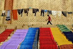 Colorful Walk. A dhoba is drying the clothes on the bank of river Ganga at Varanasi , Uttarpradesh on a brighht sunny morning as per their daily routine Royalty Free Stock Photo