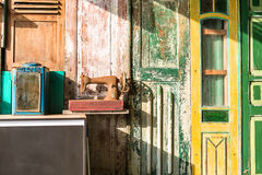 Colorful wall decorated with doors. Multi-colored wall decorated with shabby wooden doors. There is a stand with an old box with mirror and a rusted sewing stock images