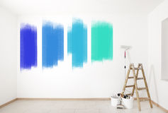 Colorful wall painting. A choice of bright colors on a wall with ladder and painting tools royalty free stock photography
